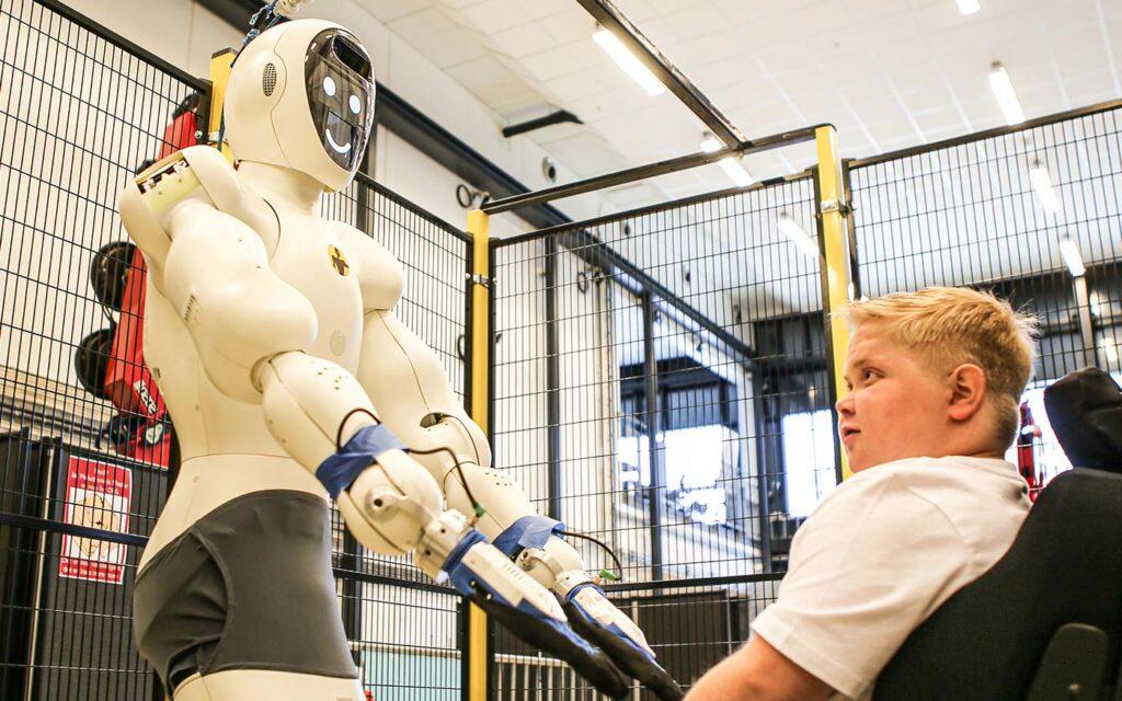 Andreas Eikin som kikker opp på roboten EVE