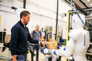 Her viser UiA-student Kristoffer Sand hvordan roboten EVE fungerer i praksis til Andreas Eikin og lærer Emil Evnum fra Dahlske videregående skole.
