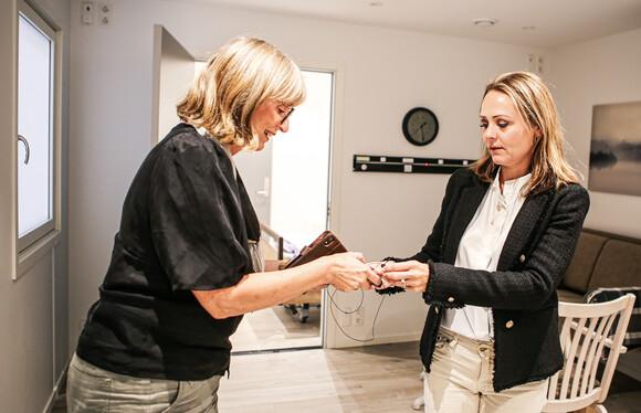 Administrerende direktør i i4Helse, Inger Holen, gir statsråd Linda Hoftsad Helleland (t.h) en mikrofon til å høre og passe på statsrådens puls, pust og tilstedeværelse i testrommet.